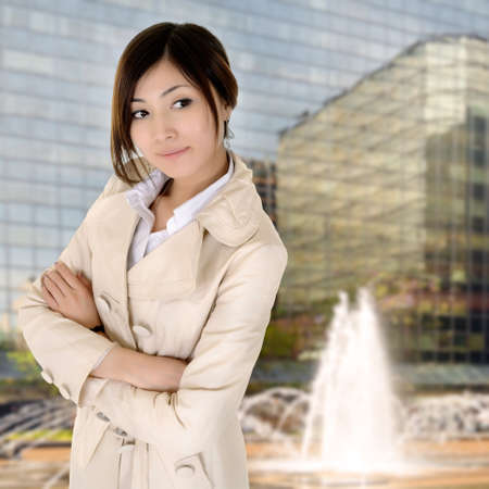 Successful young executive woman of Asian standing with modern building exterior.
