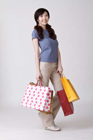 Happy smiling shopper of Asian young woman against studio gray background. Stock Photo - 8911419