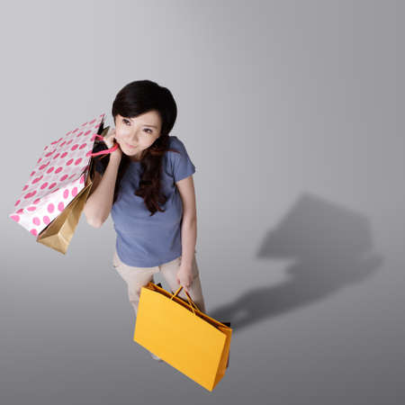 Cheerful shopping woman holding bags in studio background of gray. Stock Photo - 8911413