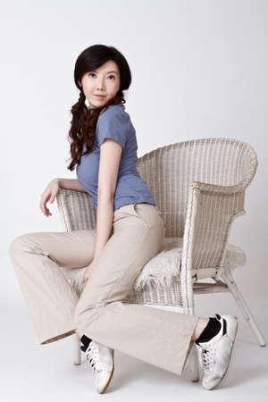 Aantrekkelijke jonge Aziatische vrouw zitten op de stoel met mooie uitdrukking van gezicht.