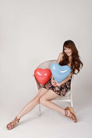 sit: Cheerful smiling lady holding heart shaped balloon and sitting on chair.
