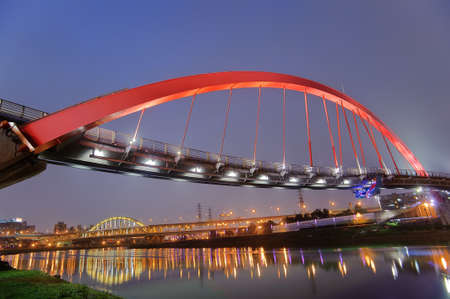 Colorful bridge over river in Taipei city night, Taiwan. photo