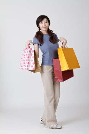 Young woman shopping, full length portrait on gray studio background. Stock Photo - 9041807