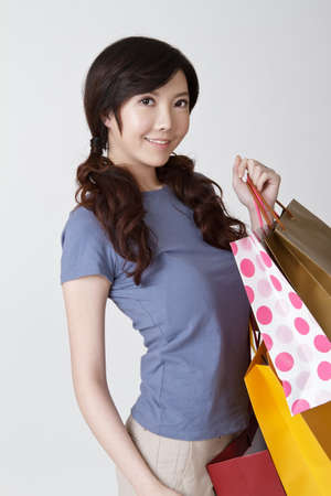Smiling shopping woman of Asian, closeup portrait on gray background. Stock Photo - 9041885