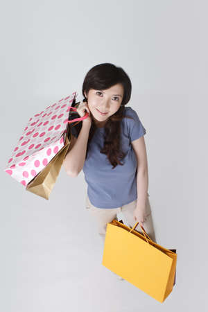 Shopping woman holding bags with smiling face looking at you. Stock Photo - 9041873