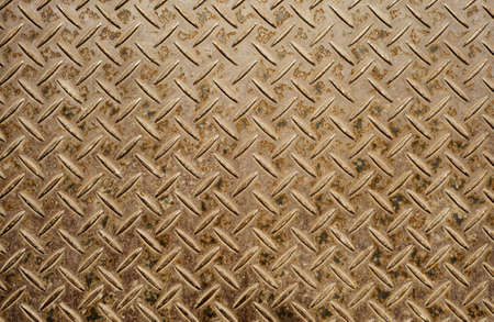 Background of old and grungy metal diamond plate in brown color.  photo