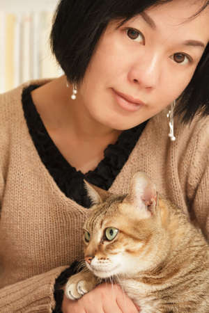 dwell: Woman with her cat of pet in home and looking at you. Stock Photo