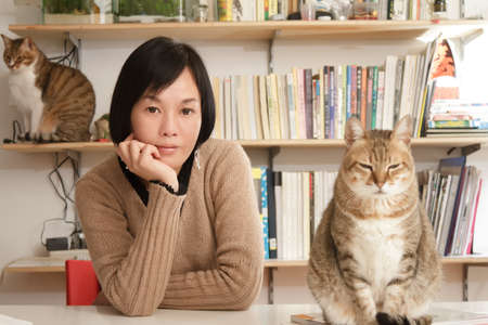 single dwelling: Woman with her cats in home, focus on the woman. Stock Photo