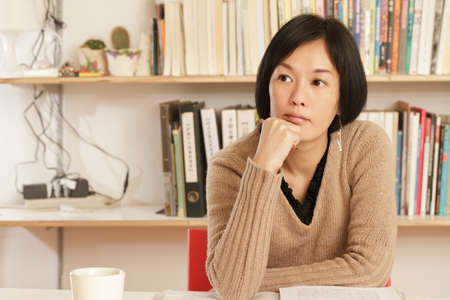 Woman sitting and thinking at home with copyspace. photo