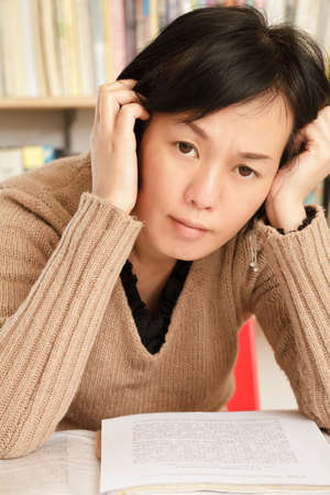 dwell: Worried mature Asian woman sitting and looking at you. Stock Photo