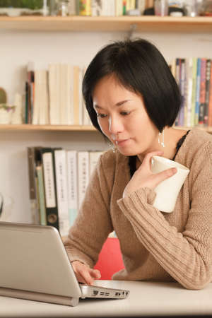 dwell: Woman using laptop on desk and holding a cup of tea at home.