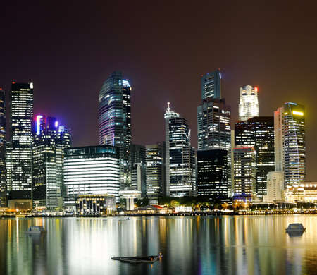 Night scene of modern city with buildings and river in Singapore, Asia. photo