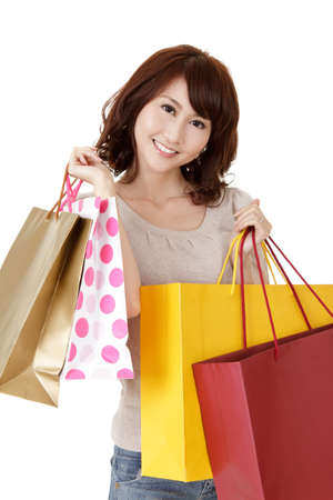 Smiling shopping woman of Asian, closeup portrait of young lady holding bags on white background. Stock Photo - 9113904
