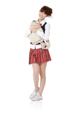 Adorable school student girl of Asian carry schoolbag, full length portrait isolated on white background. Stock Photo - 9113871