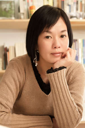 Mature woman of Asian at home, closeup portrait inside of house. photo