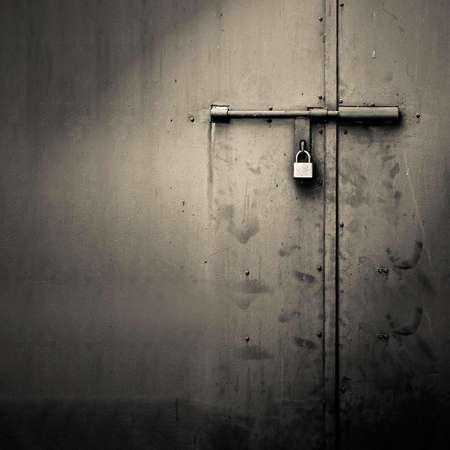Background of door with lock in metal material and copyspace on wall. Stock Photo