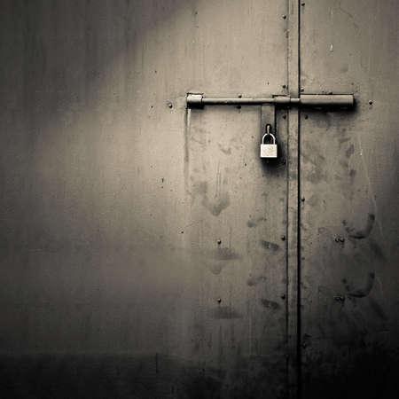 travar: Background of door with lock in metal material and copyspace on wall. Banco de Imagens