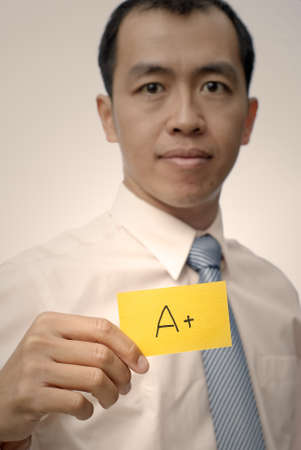 Mature executive of Asian holding A plus card in yellow, half length closeup portrait. photo