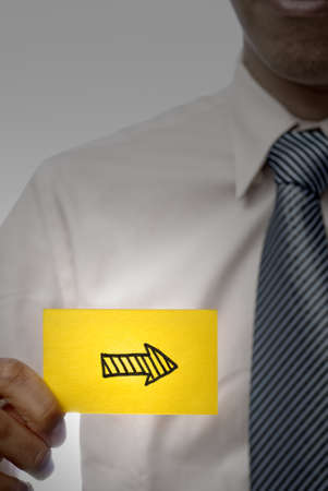 Business man holding right arrow shape on yellow card, closeup portrait. photo