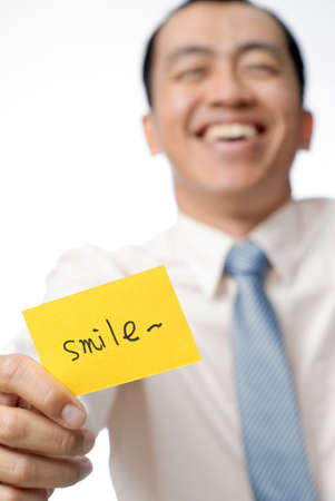 Happy businessman of Asian holding yellow card written smile words, closeup portrait. photo