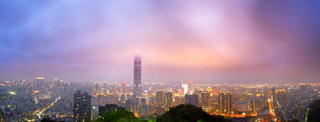 Cityscape of Taipei with dramatic colorful clouds on sky and famous skyscraper in night in Taiwan in panoramic.