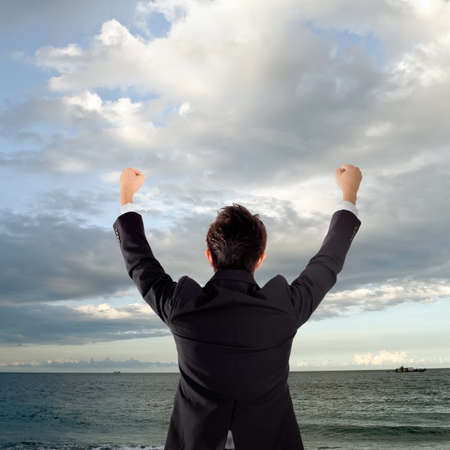 excitacion: Hombre de negocios alegre permanente fuera del oc�ano y aumentando las manos. Foto de archivo