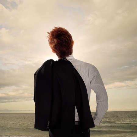 야외에서 서 있고 멀리 바다의 찾고 피곤 된 비즈니스 남자.