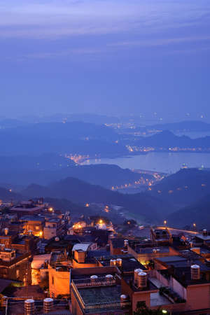 taiwan scenery: City night scene with houses on hill in yellow tone under blue sky in Jiufen(Jioufen), Taiwan, Asia.