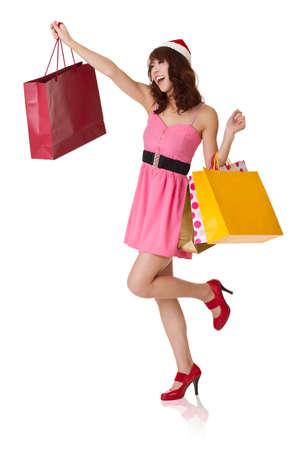 chicas compras: Chica compra feliz celebración de bolsas y con sombrero de Navidad buscando retrato de longitud lejana, completa aislada sobre fondo blanco.