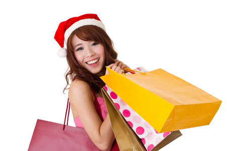 leisure centre: Happy shopping girl holding bags and wearing Christmas hat, half length closeup portrait on white background.