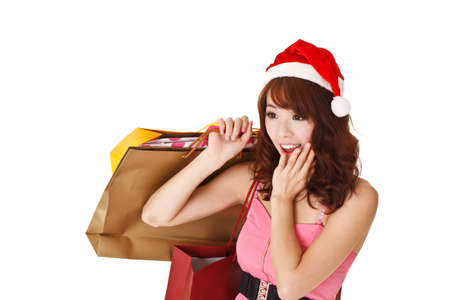 Happy shopping girl holding bags and wearing Christmas hat with surprised expression, half length closeup portrait on white background. photo