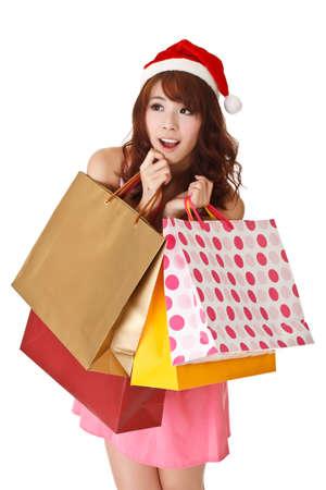 compras chica: Chica compra feliz celebraci�n de bolsas y con sombrero de Navidad, retrato de detalle de media longitud sobre fondo blanco. Foto de archivo