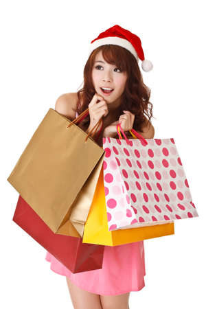 asian girl shopping: Happy shopping girl holding bags and wearing Christmas hat, half length closeup portrait on white background.