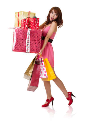 Happy shopping girl holding bags and gift box, full length portrait isolated on white background.