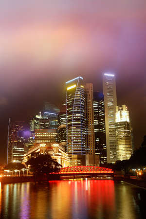 Colorful city night scene with skyscrapers near river in Singapore, Asia. photo