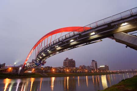 Beautiful bridge in red color over river in evening, city night scene in Taipei, Asia. Stock Photo - 9410062