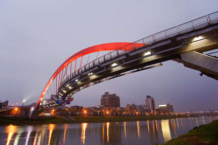 Beautiful bridge in red color over river in evening, city night scene in Taipei, Asia. Stock Photo - 9410062