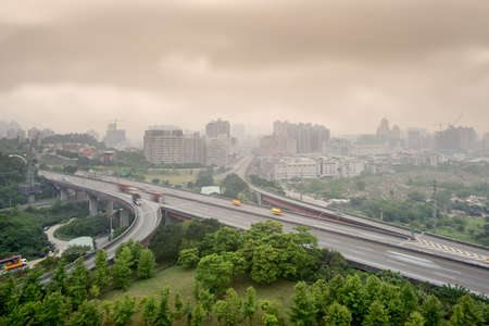 building external: Sunset cityscape of highway and buildings with bad weather and air pollution, city scenery in Taipei, Taiwan.