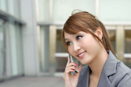 Attractive business woman using cellphone, half length closeup portrait in outside of modern buildings. photo