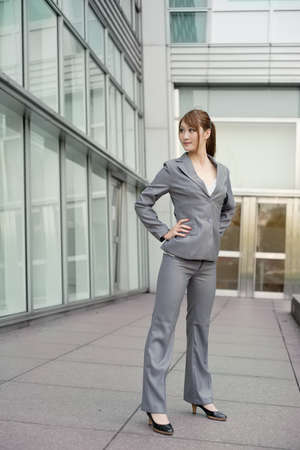 Confident business executive standing and looking, full length portrait outside of modern buildings. photo