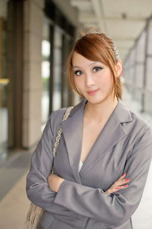 kindly: Kindly business woman standing in corridor and looking at you, half length closeup portrait outside of modern buildings.