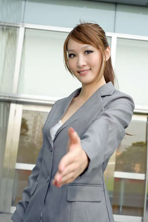 Young business manager shaking hand with you, half length closeup portrait outside of modern buildings. photo