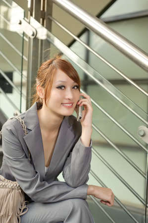 elegant staircase: Young business manager woman holding cellphone and sitting, half length closeup portrait outside of modern buildings.