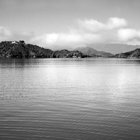 Nature landscape of lake with mountain and water under sky in black and white tone.