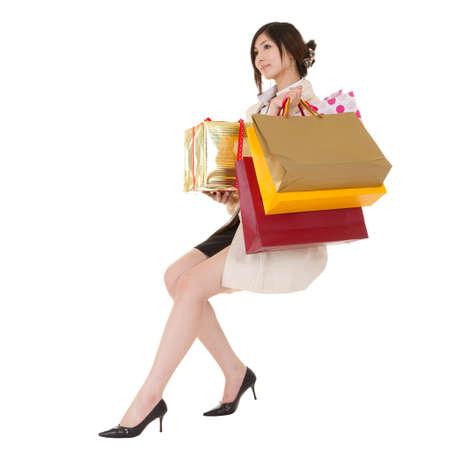 Aislado sentado compra mujer sosteniendo bolsas y caja de regalo, retrato de larga duración sobre fondo blanco.