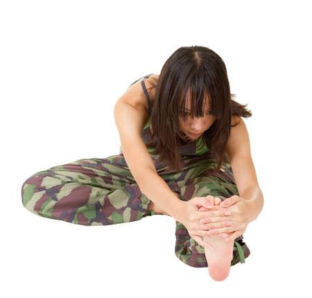 excise: Donna palestra facendo elasticizzata accise sul terreno, ritratto di lunghezza isolato su sfondo bianco.