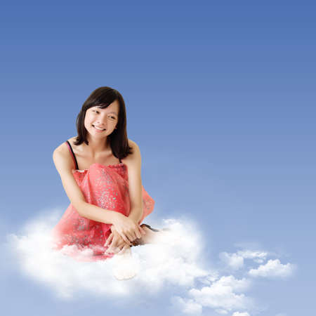 Chinese girl sitting on clouds over blue sky with peaceful and thinking expression on face. photo