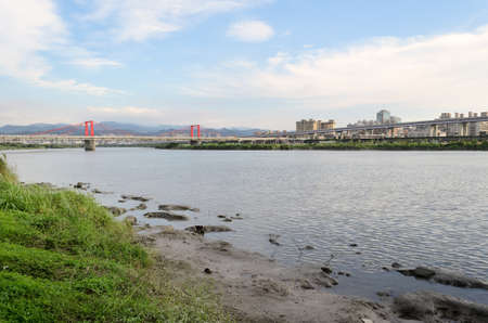 River in city under blue with bridge far away in Taipei, Taiwan, Asia. Stock Photo - 9789911