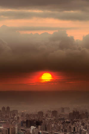Sunset city scenery with red sun over buildings and clouds in Taipei, Taiwan, Asia. Stock Photo - 10021294