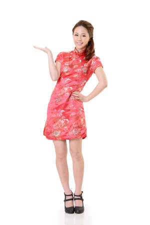 Smiling Chinese woman dress traditional cheongsam and introduce on white background. photo